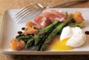 Grilled asparagus, prosciutto, fried bread, and poached egg on a white plate with a fork resting on the side.