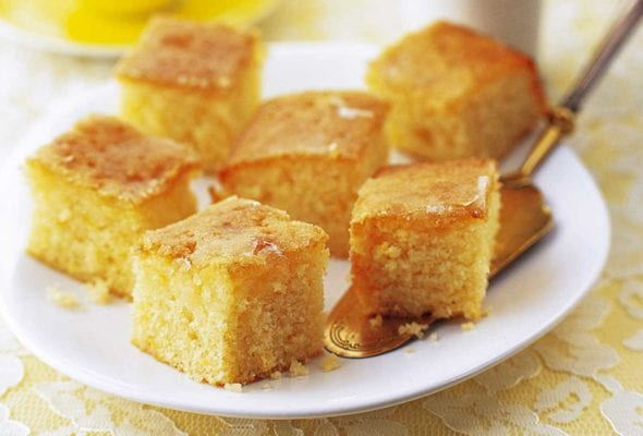 Squares of lemon drizzle cake on a white plate with a cake server resting underneath and a cup of tea and vase of flowers in the background.