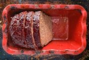 Half a cooked meatloaf in a red loaf tin with two slices cut from it.