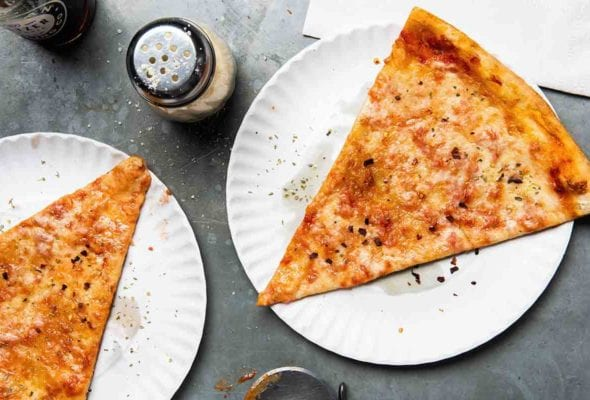 Two slices of New York style pizza on paper plates with a cheese shaker and napkins beside the pizza.