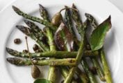 A white plate topped with roasted asparagus with bay leaves and crispy capers.