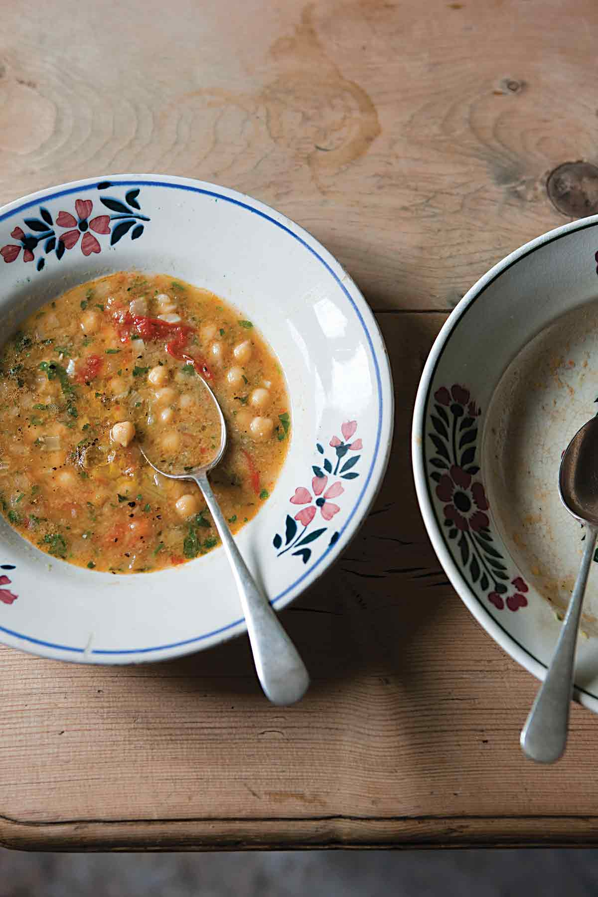 Two bowls, one filled with smoked paprika and chickpea soup, with a spoon resting inside, and the other bowl empty.