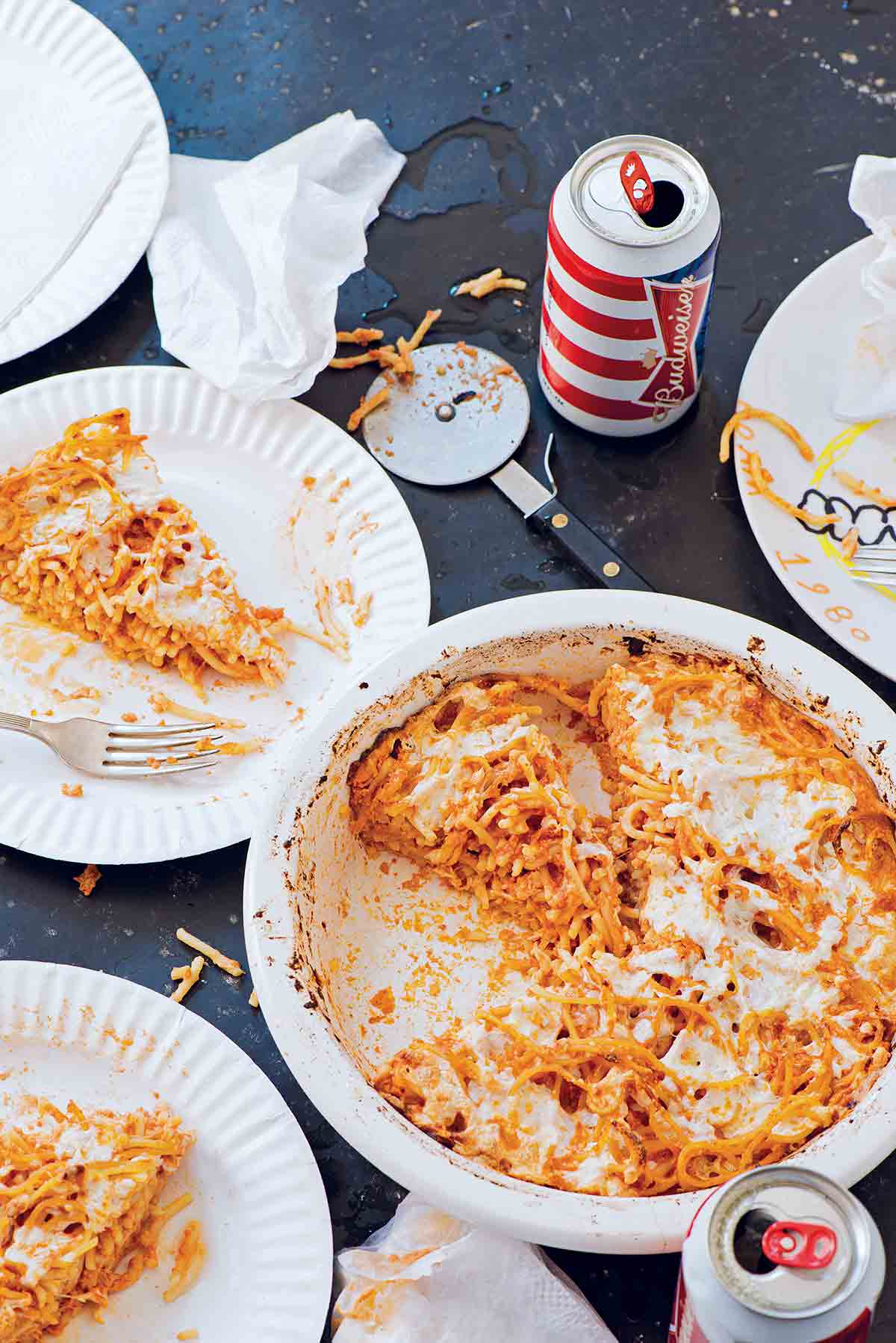 A white dish with a partially cut spaghetti pie, two paper plates with slices of spaghetti pie, a pizza cutter, napkins, and two cans of beer.