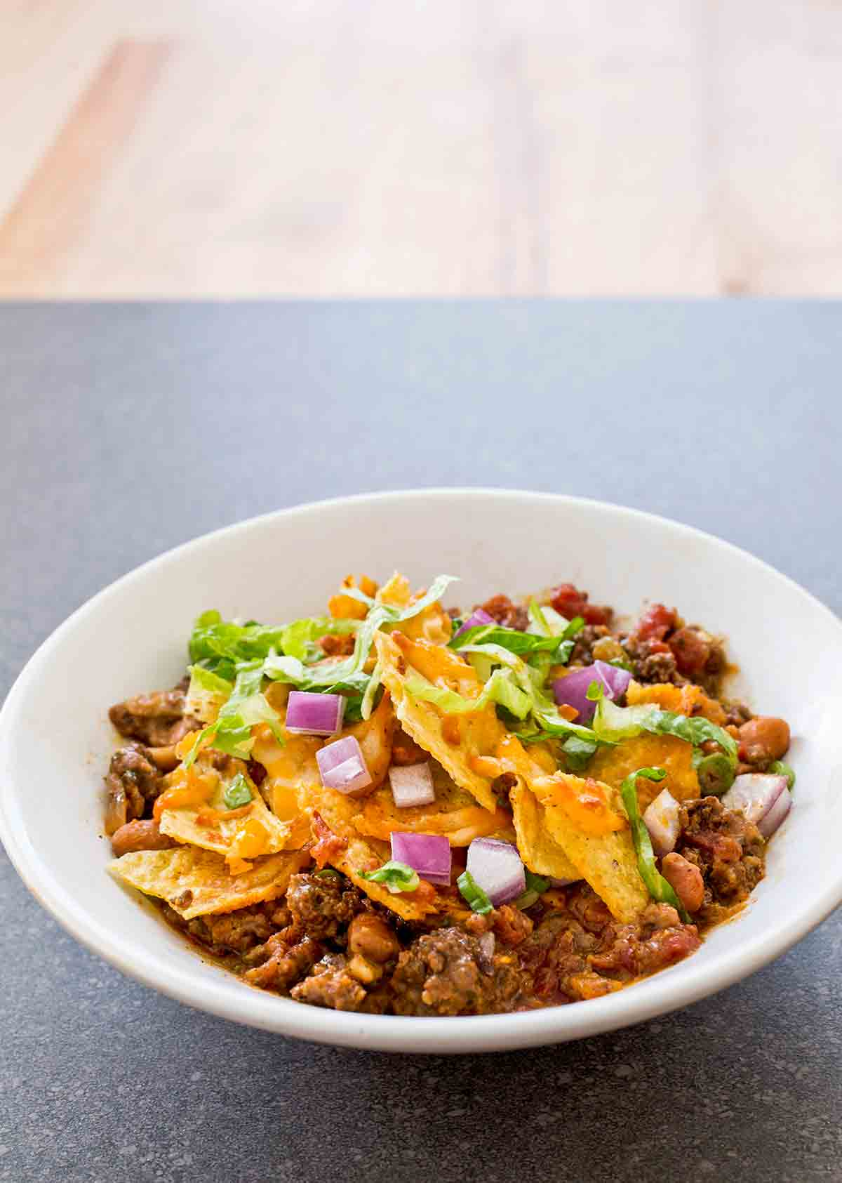 White bowl of spicy beef taco bake with ground beef, beans tortilla chips, chopped onions, and lettuce
