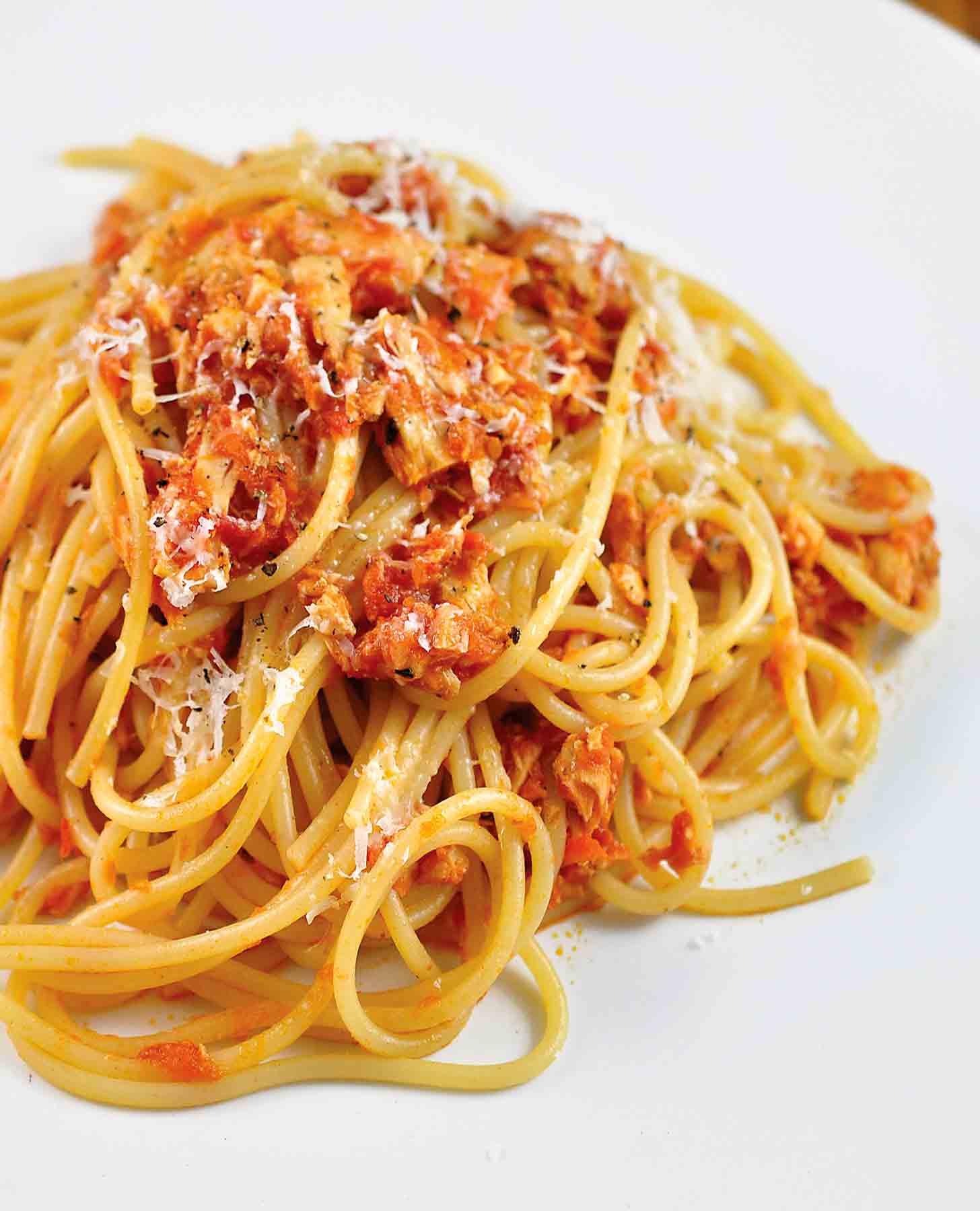 A tangle of tomato and tuna spaghetti on a white plate.