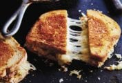 Three turkey reuben patty melts - one in a cast-iron skillet, and two on a dark surface, one sliced diagonally.