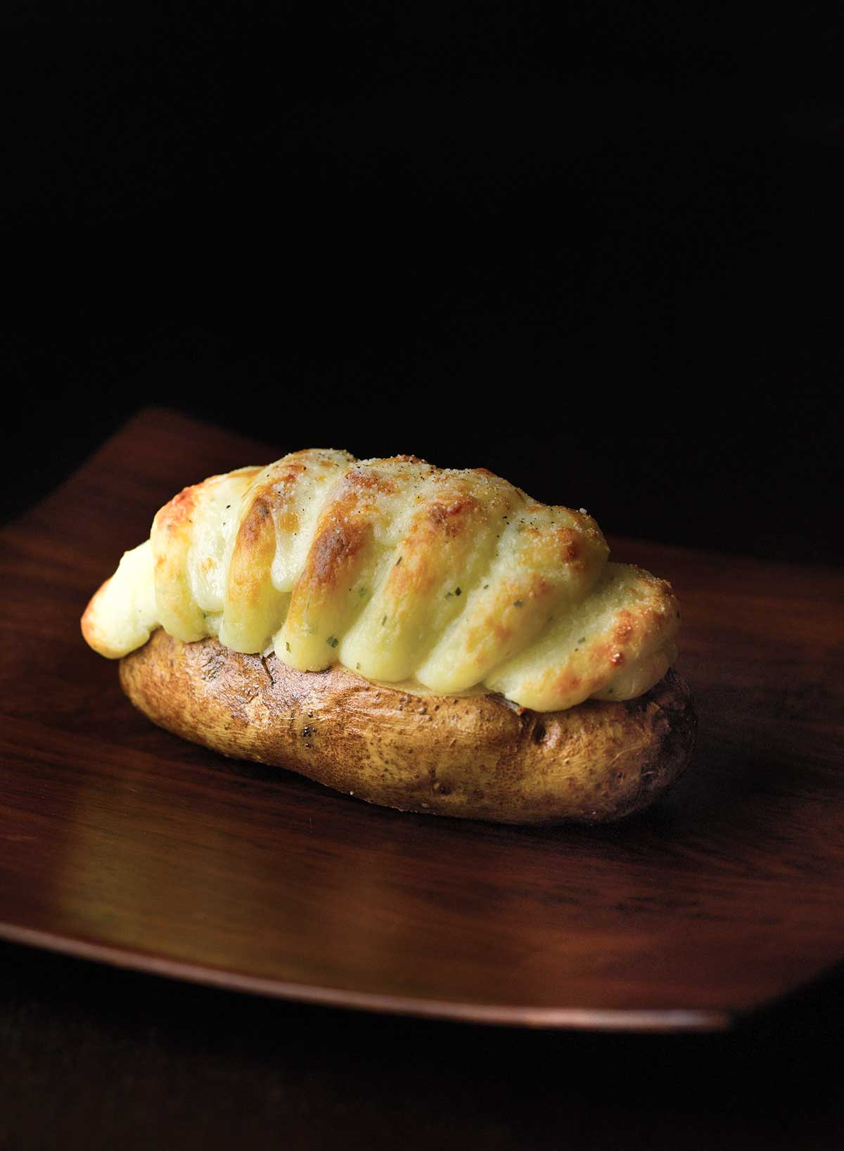 A twice-baked potato with Irish Cheddar on a dark wood table.