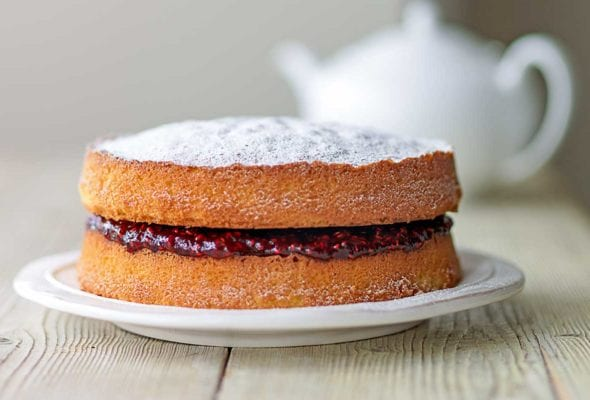 A two-tier Victoria sponge cake with raspberry jam in the middle, all dusted with confectioners' sugar on a white plate with a white teapot in the background