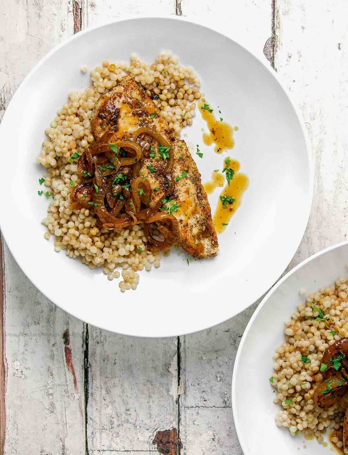 Two white plates each topped with a serving of za'atar chicken, Israeli couscous, sauteed onions, and pan juices.