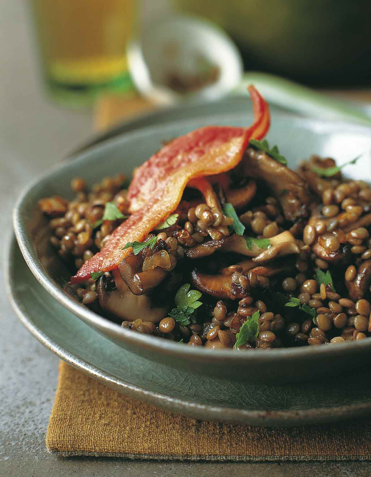 A green bowl filled with sautéed bacon, mushrooms, and lentils with a whole piece of bacon on top.