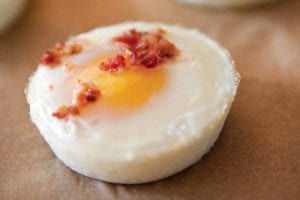 Four baked eggs sprinkled with chopped bacon.