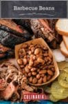 A paper contain of barbecue beans and pulled pork, surrounded by hunks of smoked meats