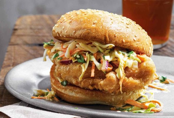 A beer battered chicken sandwich topped with slaw on a white plate on top of a paper napkin on a wooden table with a glass of beer in the background.