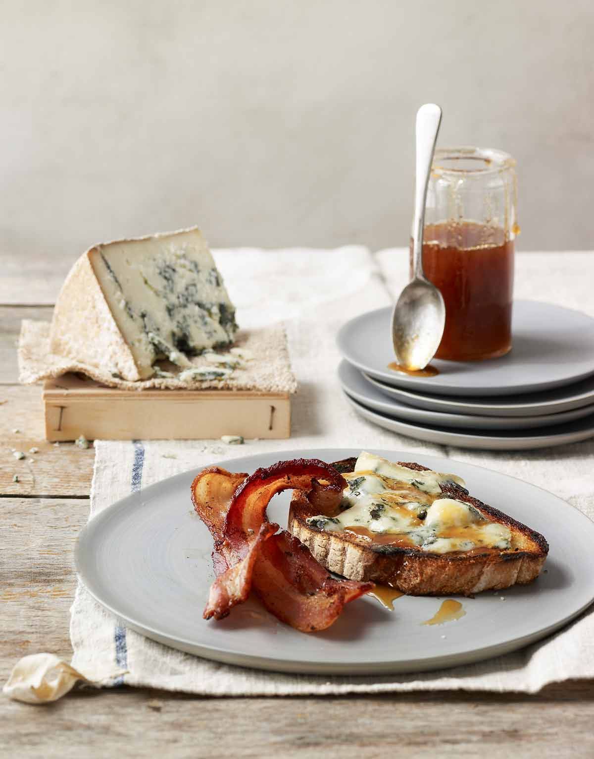 A piece of blue cheese tartine with two slices of crispy bacon on a grey plate.