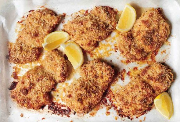 Six breaded oven fried chicken thighs with four lemon wedges in a parchment-lined dish.