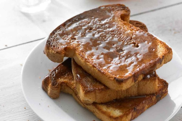 Three slices of cinnamon toast stacked on a white plate.