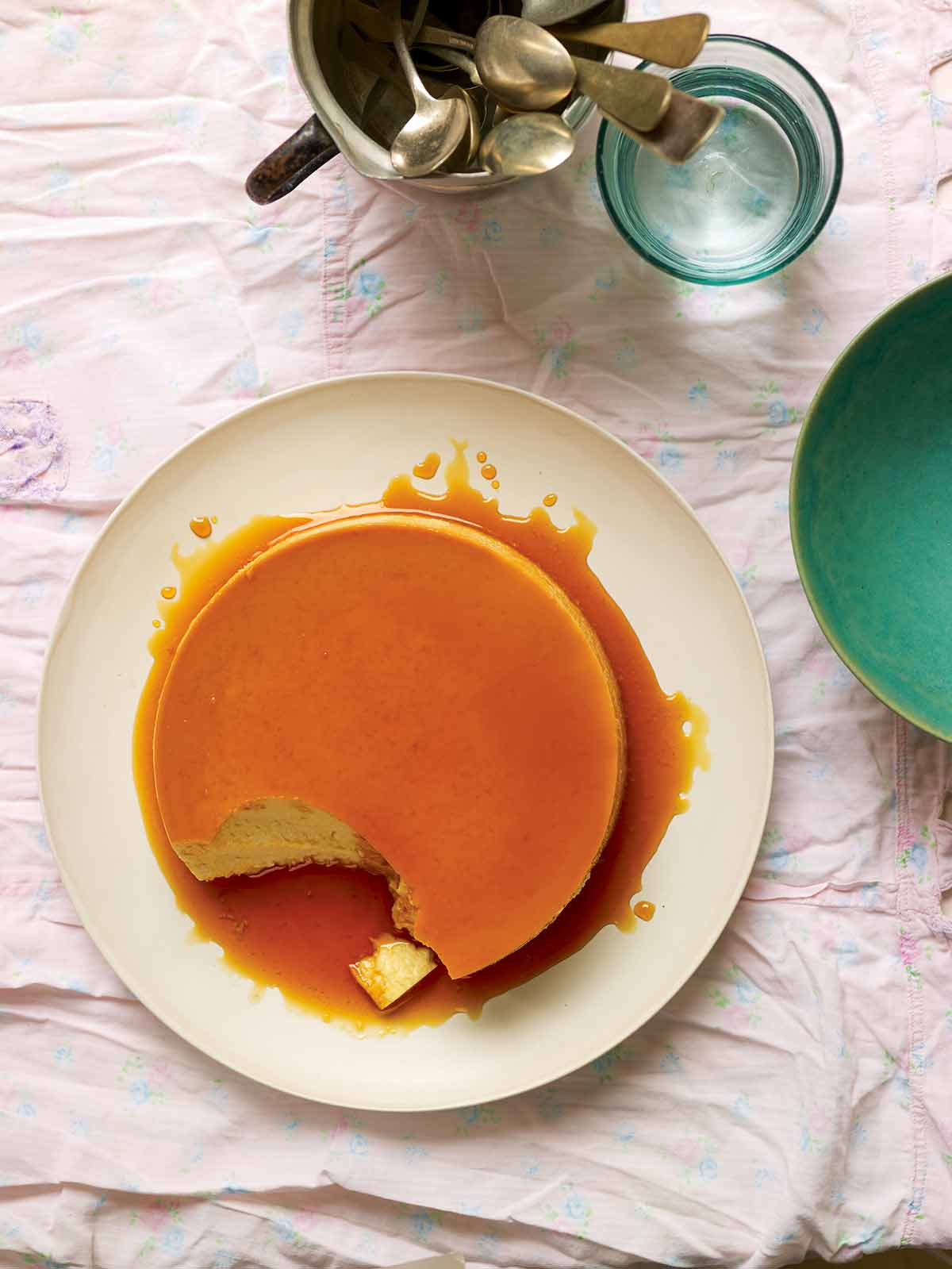 A classic flan de leche on a white plate, covered with caramel and a spoonful of custard missing from the flan.