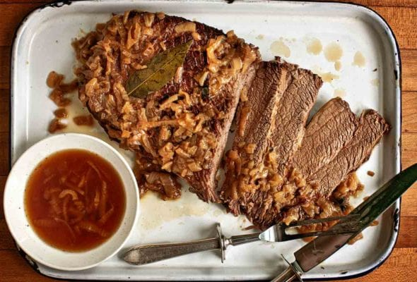 An enamel baking dish holding a sliced oven brisket topped with onions with jus on the side.