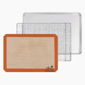 The French Pantry 3 piece baking gift set consisting of a half-sheet pan, silicone baking mat, and a cooling rack.
