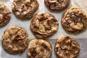 Several ginger chocolate chunk cookies on a piece of parchment paper.
