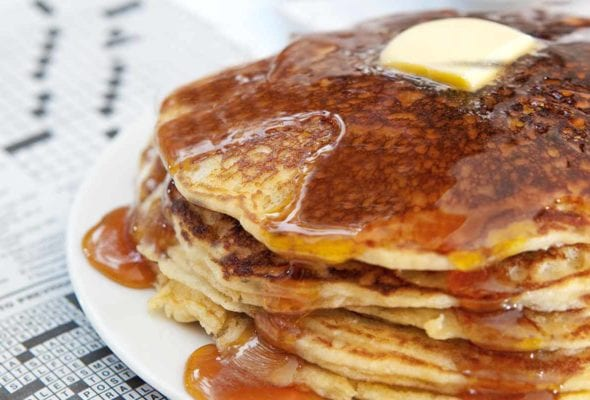 A stack of gluten-free pancakes with butter and maple syrup on a white plate on top of a crossword puzzle.