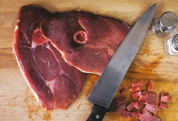 A slice of ham with red eye gravy on a cutting board with a knife and salt and pepper shaker.