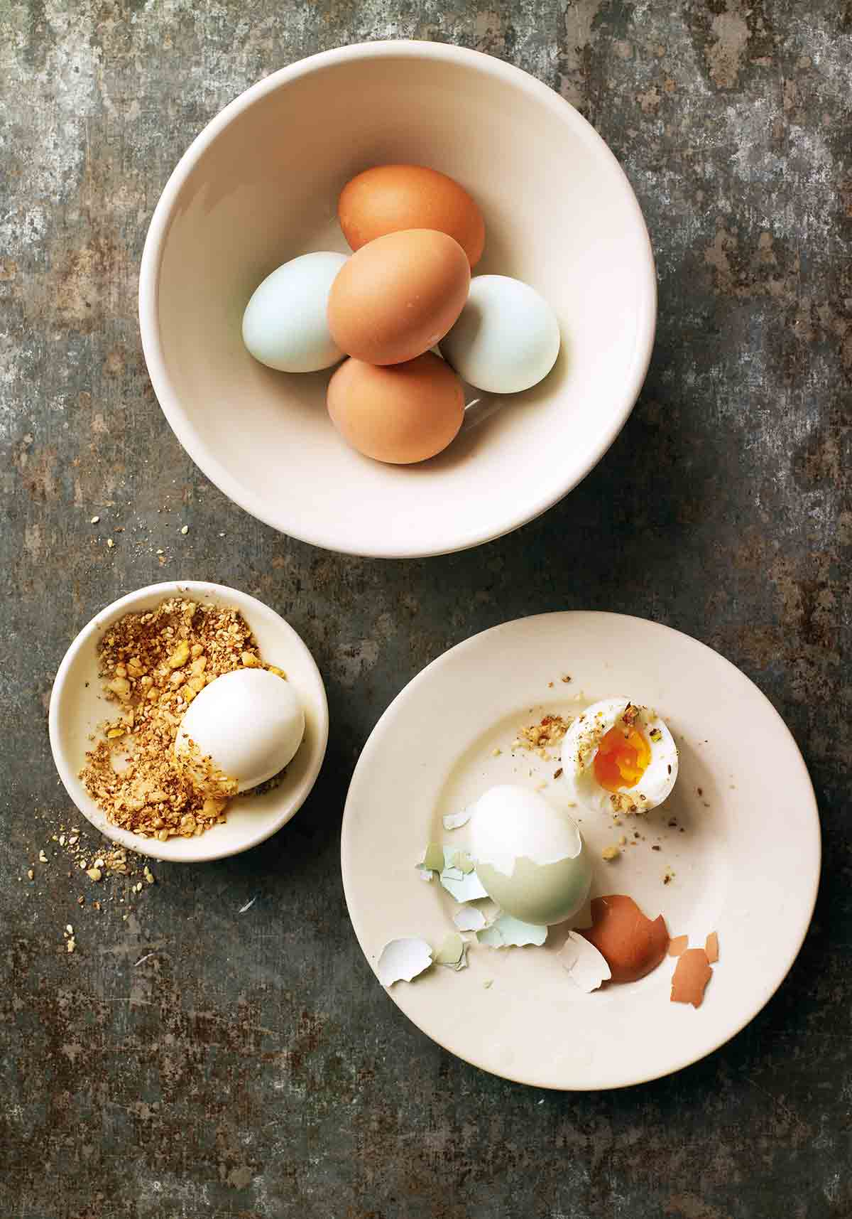 A bowl of hard-boiled eggs with dukkah in a bowl next to it.