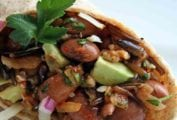 A pinto bean, quinoa, and wild rice wrap, cut in half and garnished with a sprig of parsley.