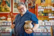 Steve Sando holding an earthenware vessel and wooden spoon.