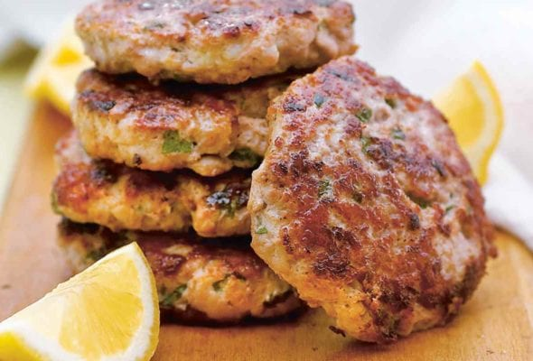 Five turkey burgers with lemon and mint stacked on a wooden board with lemon wedges.