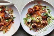 Two shallow bowls filled with turkey meatballs with rice noodle salad and a pair of chopsticks rests on the side of each bowl.