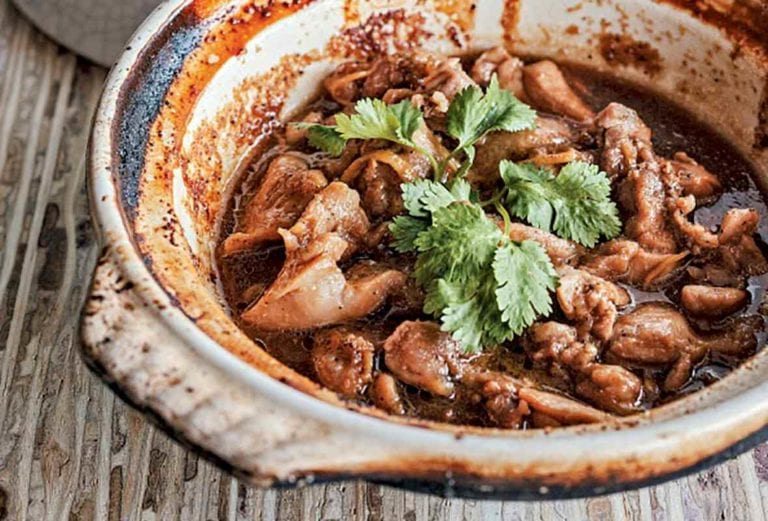 Clay pot filled with Vietnamese caramel chicken pieces and cilantro on a wooden table