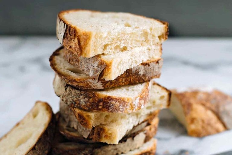 Halved slices of sourdough stacked on top of each other on a white and grey marble surface.