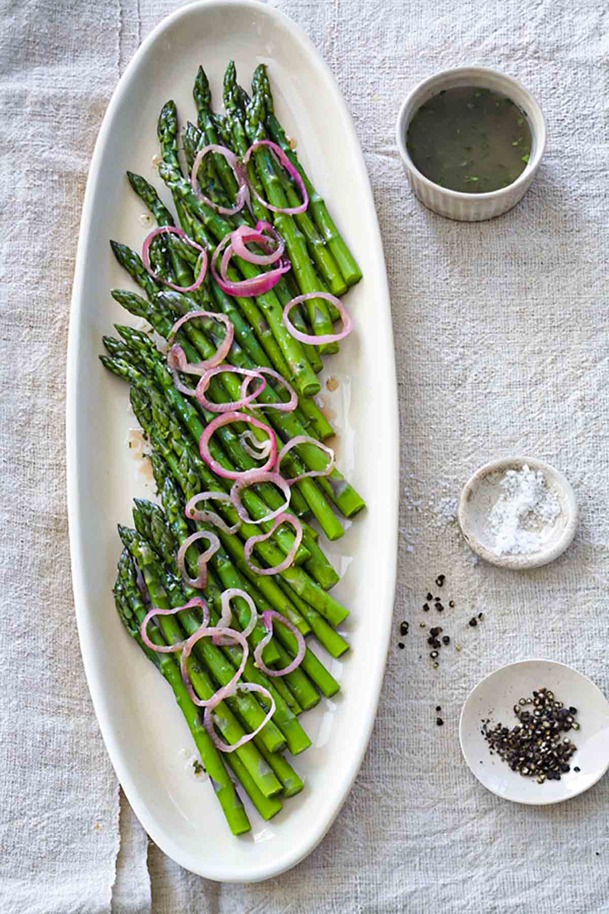 A white oval platter filled with asparagus with raspberry-shallot vinaigrette, and pickled shallots scattered on top.