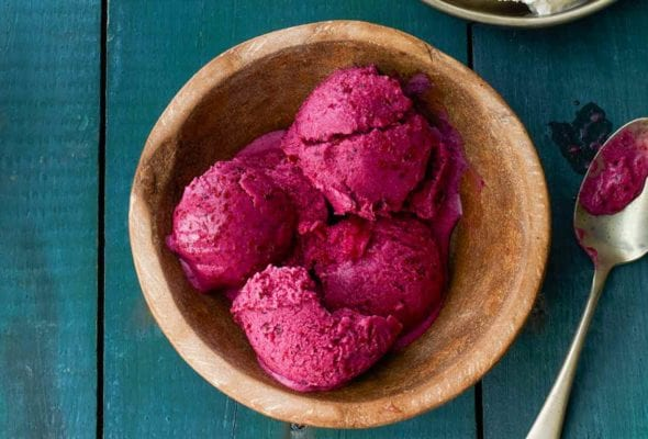 Four scoops of blueberry frozen yogurt in a wooden bowl with a spoon resting beside it.
