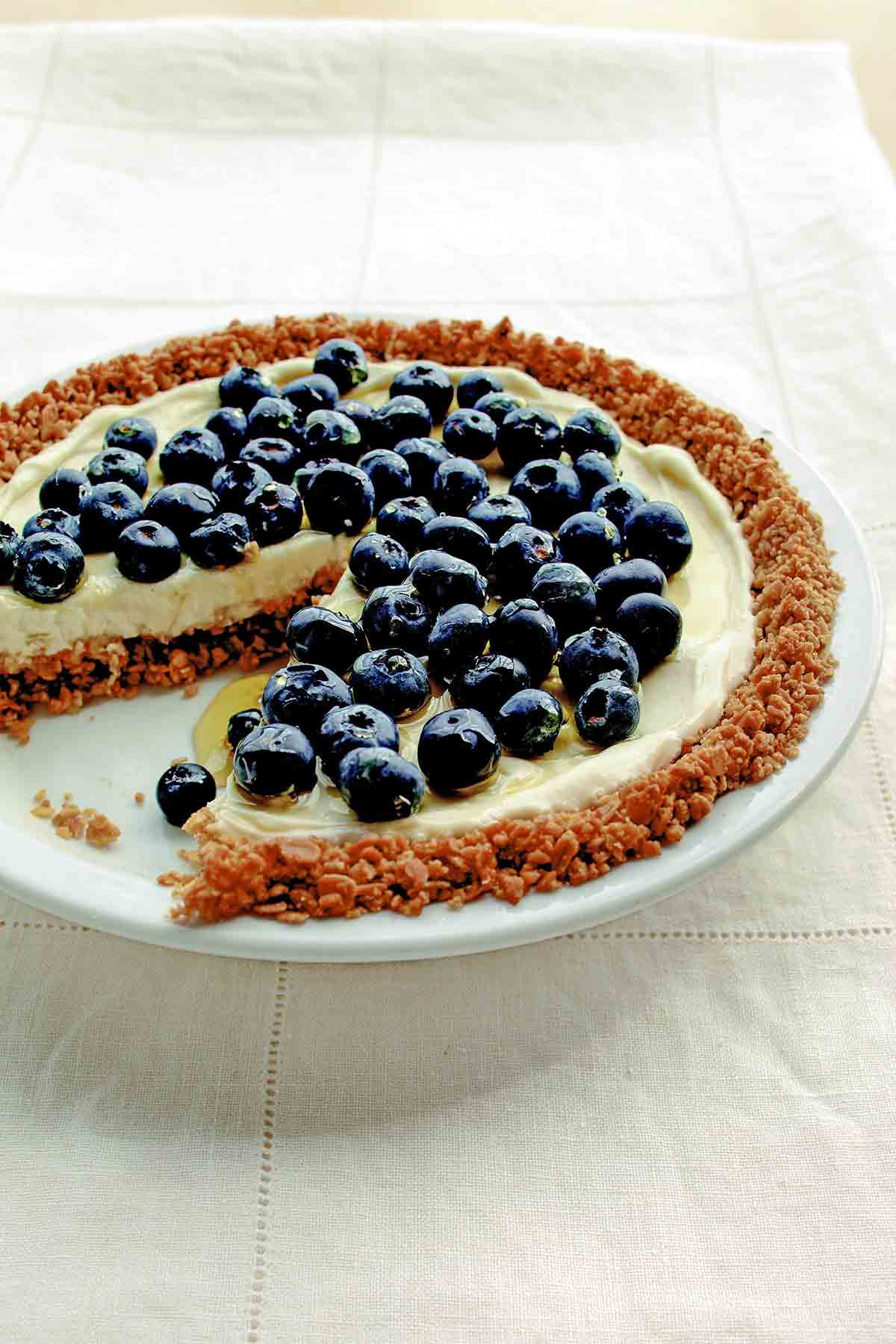 A blueberry pie with granola crust and blueberries on top with one slice missing.