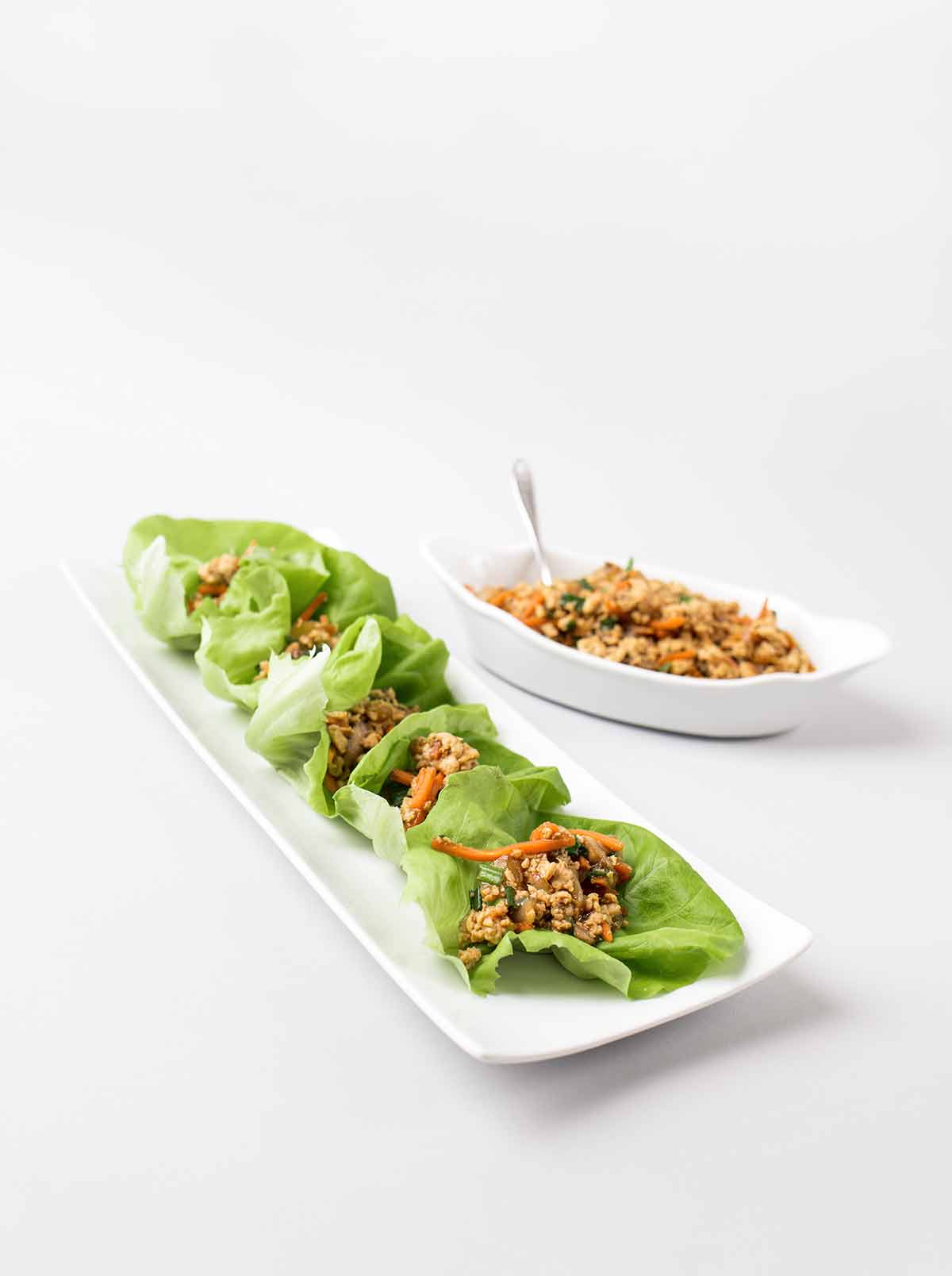 A rectangular plate with six Chinese chicken lettuce wraps and a bowl of extra filling beside it.