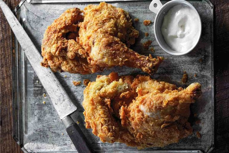 Two pieces of cornmeal-crusted fried chicken with white barbecue sauce and a knife on a metal sheet.