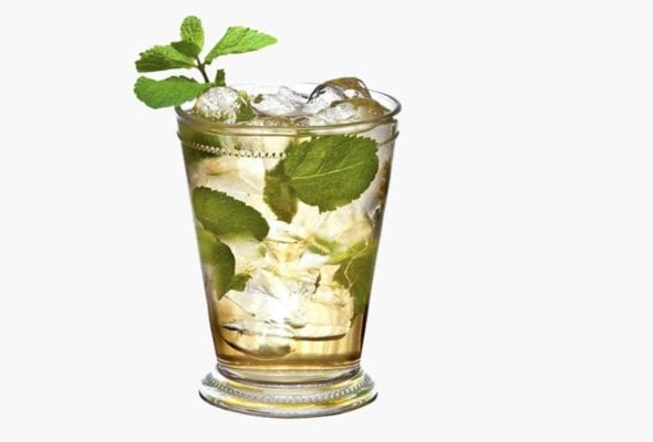 A crystal mint julep cup filled with ice, mint, and liquid.