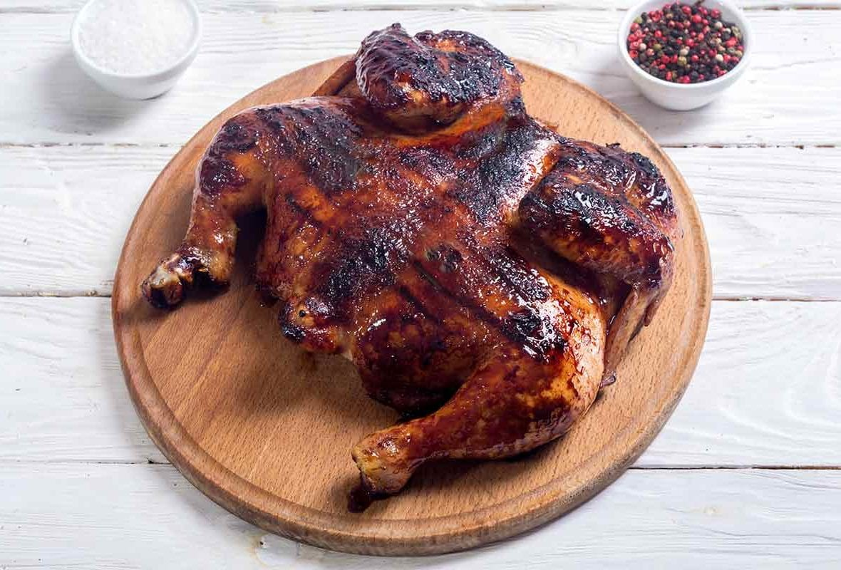 A whole spatchcocked grilled roasted chicken on a round wooden board with dishes of salt and peppercorns on the side.