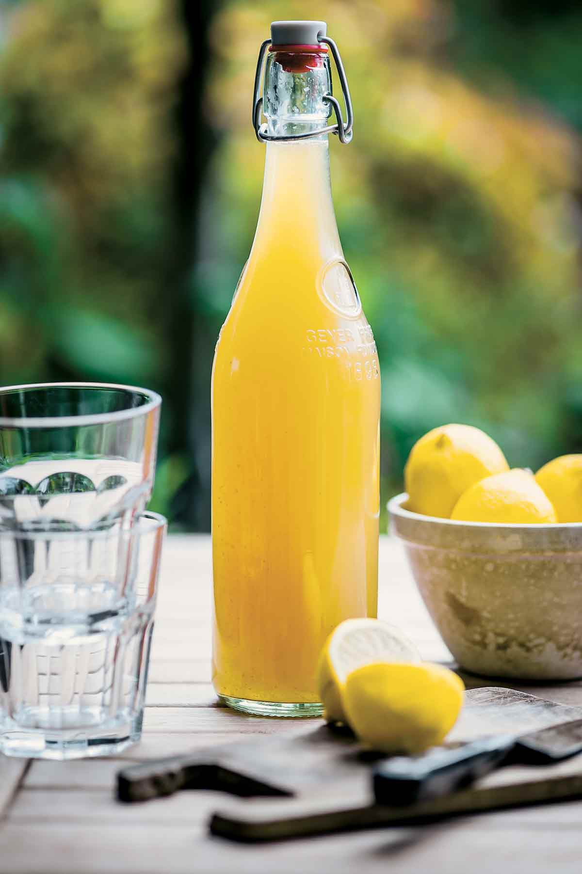 A glass bottle filled with homemade lemonade syrup, a bowl of lemons, and two glasses on a wooden table.