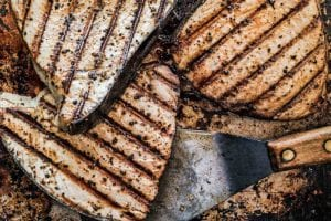 Pieces of perfectly grilled fish made with the technique explained in 'how to grill fish', on a rimmed baking sheet with a metal spatula.