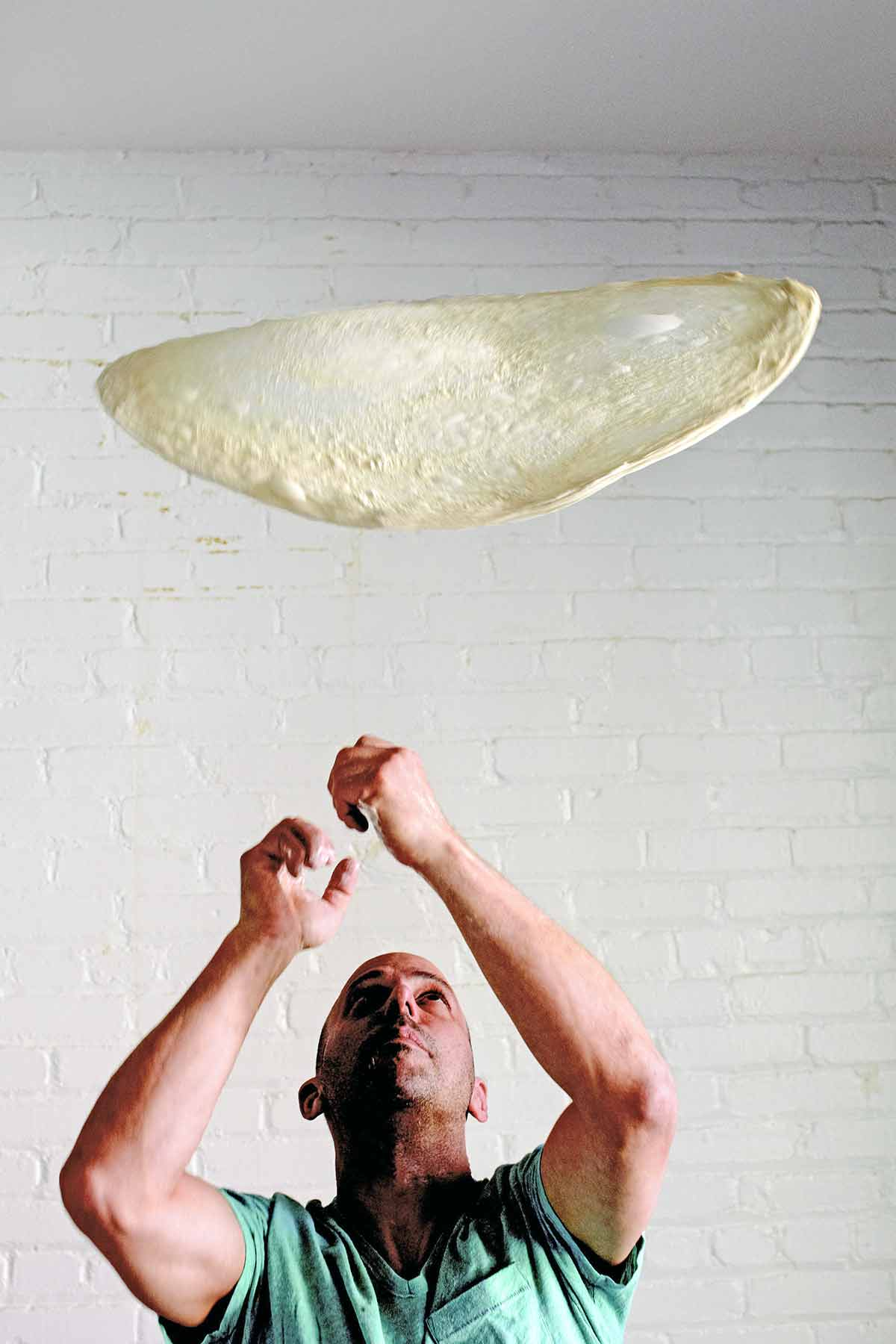 A thin circle of stretched pizza dough being tossed in the air.