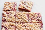 A batch of raspberry Linzer bars cut into nine squares, with one square missing and a knife in the background.