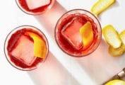 Three glasses of mezcal negroni garnished with orange peel.