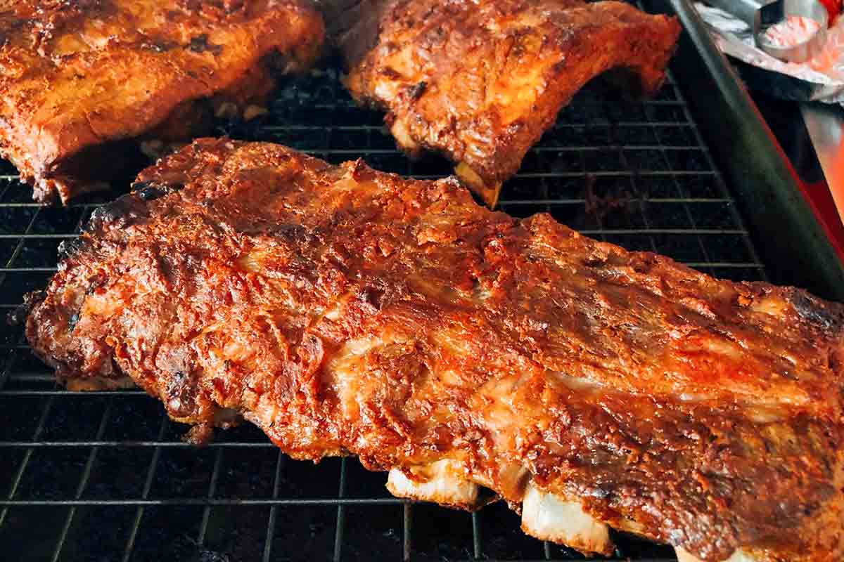 Four slabs of BBQ oven ribs on a rack inside a rimmed baking sheet.