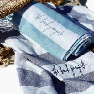 Two sand-free cabana towels inscribed with 'the beach people' lying beside a wicker basket.