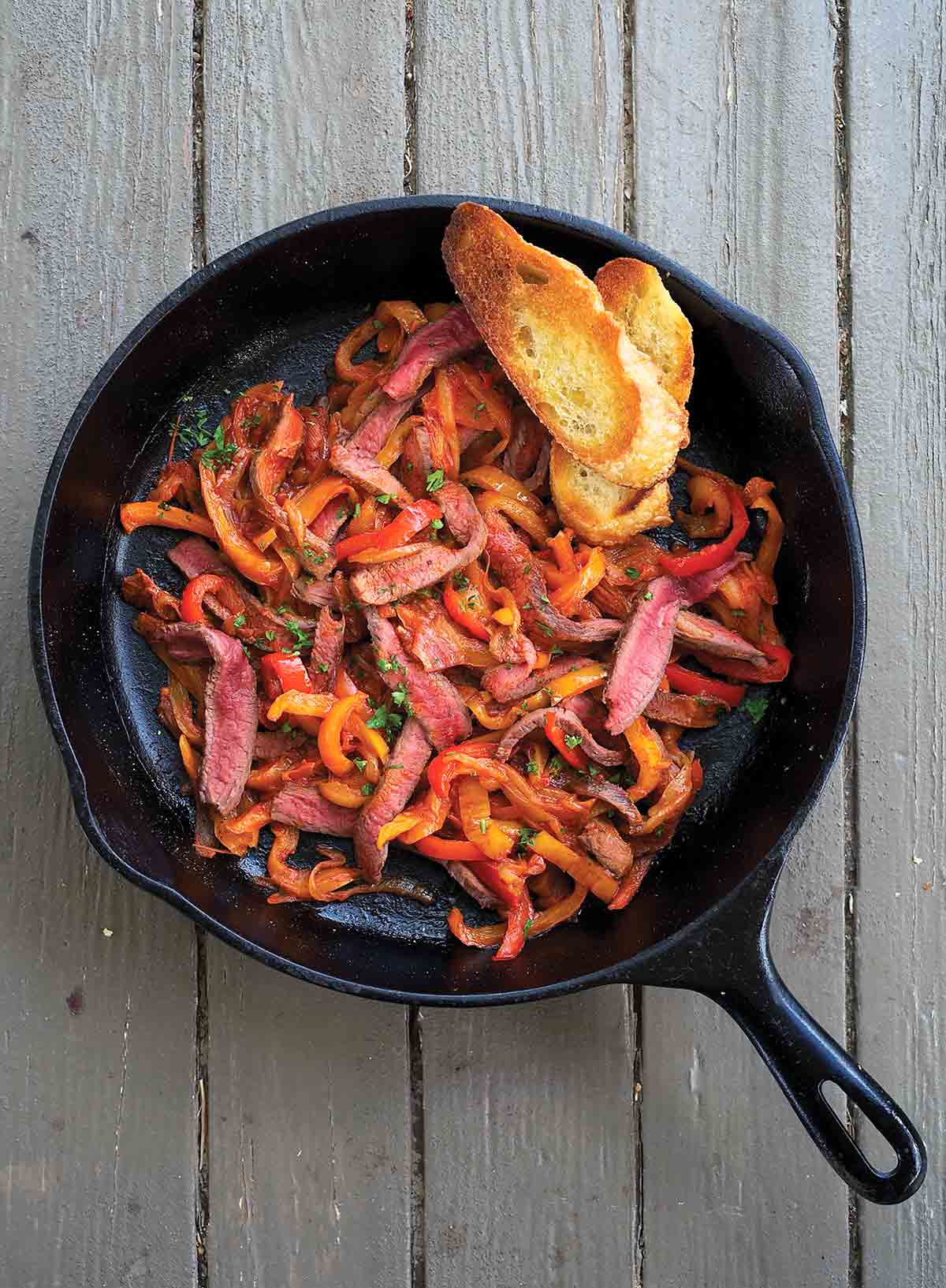 A cast-iron pan filled with skillet steak peperonata and two slices of toasted baguette.