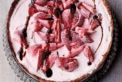 A whole strawberry ice cream pie in a fluted tart pan.