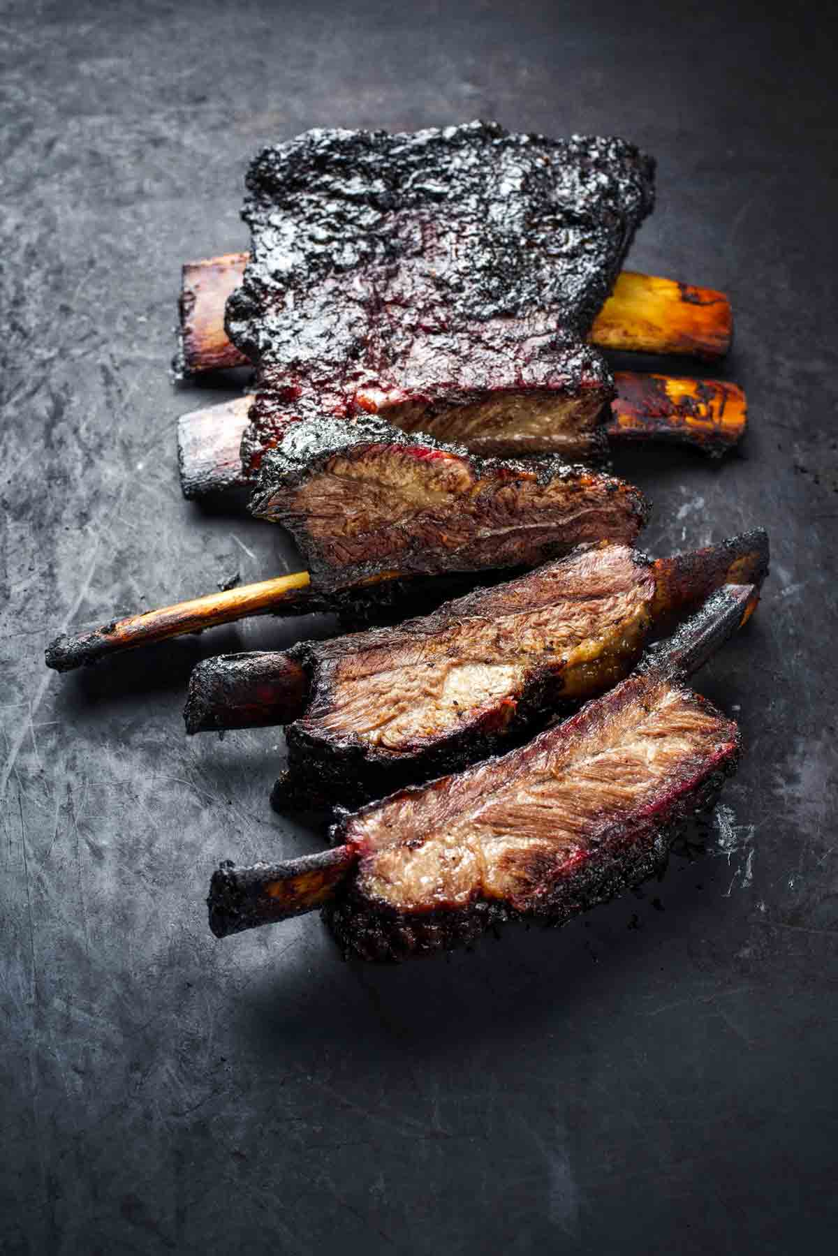 A slab of barbecued beef back ribs cut into individual ribs.